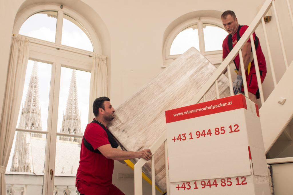 Zwei Männer bewegen Kisten die Treppe hinauf